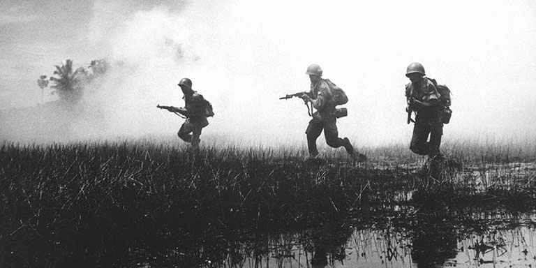 Soldiers running in a swamp