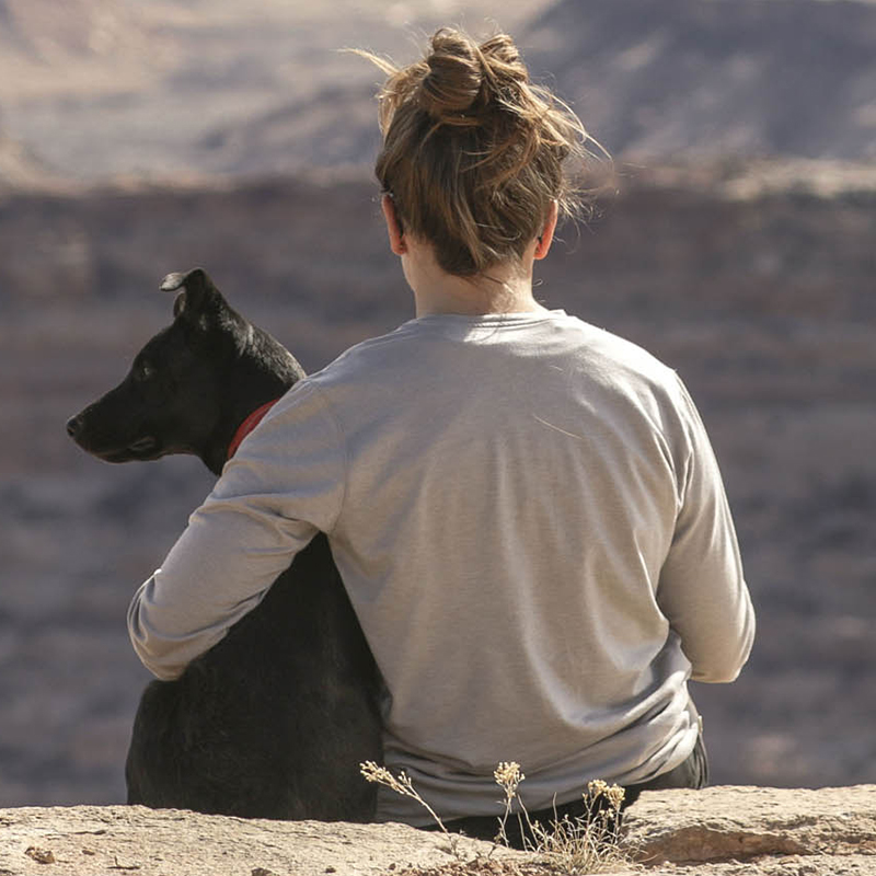a girl and dog sitting on the ledge of a mountain